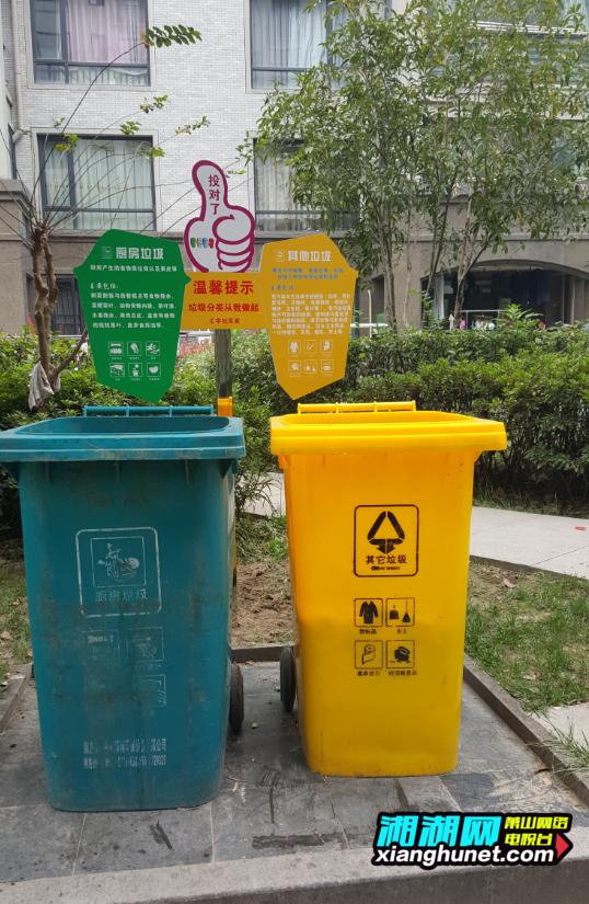 在垃圾分类桶的边上竖立了指示牌